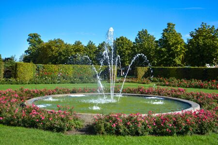 Water fountain with baroque garden in the background