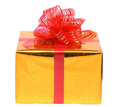 birthday present: isolated gift box in the gold package with red bow on white background. Stock Photo