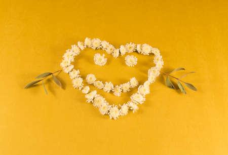 lachend hart van bloemen op een gele achtergrond.