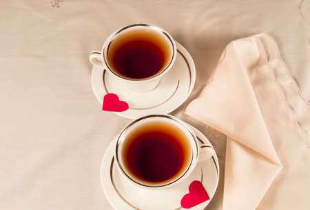 Two white tea cups on a saucer with red hearts. Reklamní fotografie
