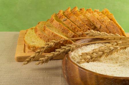 harina: El pan de molde, la harina en un plato de madera y espigas de trigo en la mesa Foto de archivo