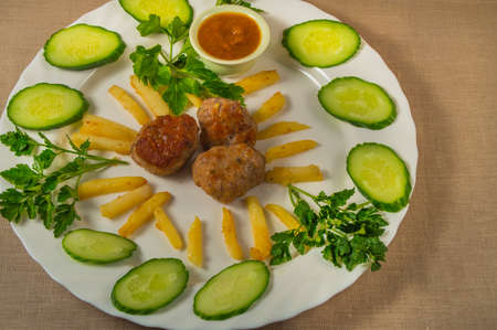 english cucumber: Fried meatballs and fried potatoes with sliced cucumbers and sauce on a white plate.