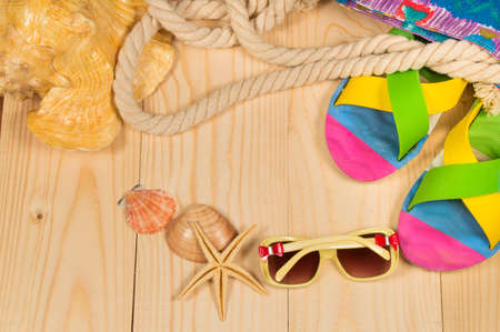 beach bag, flip flops, sunglasses, shell on wooden background. Top view