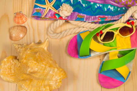 triggers: beach bag, flip flops, sunglasses, shell on wooden background. Top view