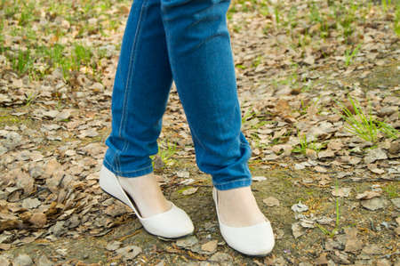 summer shoes: The girl stands, feet in jeans and light summer shoes.