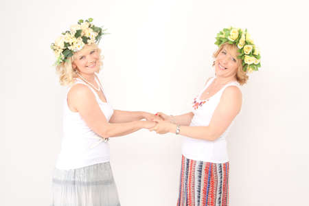 Two blonde women in flower wreaths and dancing and whirling