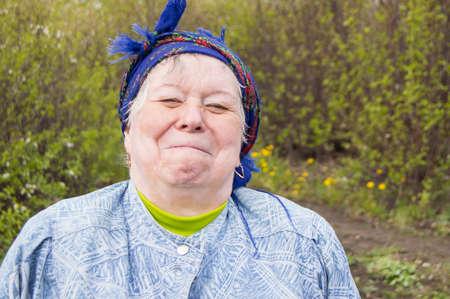 Lächelnde ältere Frau mit Kopftuch in Ihrem Garten. Standard-Bild