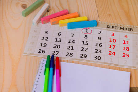 Back to school, calendar, colored chalk on wooden background. Reklamní fotografie