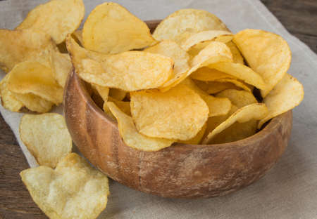 throbbing: Delicious crispy potato chips in an old wooden bowl.