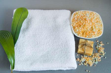 Handgemachte Seife, ein weißes Handtuch, Meersalz für die Körperpflege.