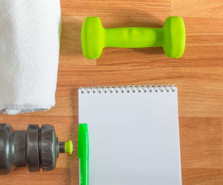 losing control: Plan workouts with dumbbells, towel, Water Bottle Notepad on wooden background