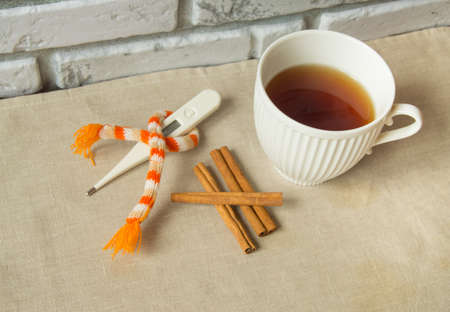 snotty: Concept of treating colds - hot tea with cinnamon, thermometer and scarf.