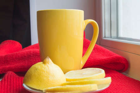 snotty: Concept of treating colds - hot tea with lemon, scarf.