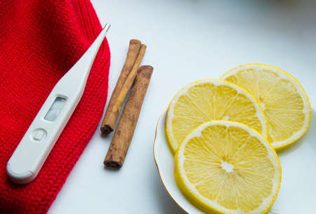 snotty: The concept of treating colds - lemon, cinnamon, thermometer scarf. Stock Photo