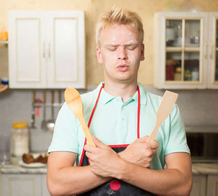 Funny young man with closed eyes holding kitchen tools. Stock Photo