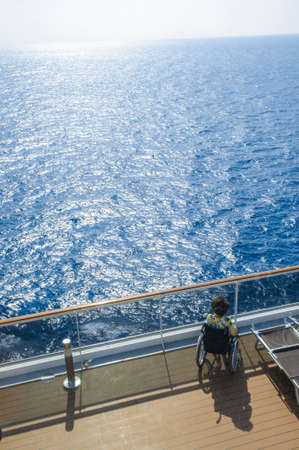 Disabled woman in wheelchair on the deck of cruise ship.