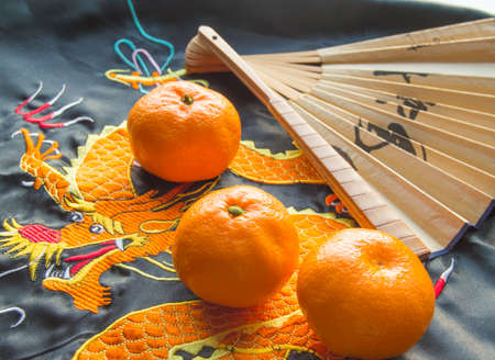 Chinese New year, tangerines and a fan lying on the silk fabric with an embroidered dragon
