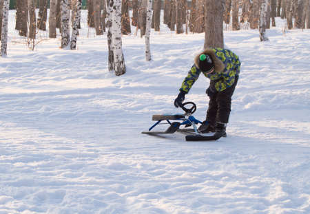 to steer a sledge: Baby boy, check the snowmobile, rolled down from the hill Stock Photo