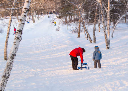 to steer a sledge: The father helps his son to correct snowmobile, rolled down hill Stock Photo