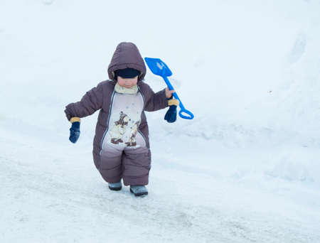 romper: Toddler boy winter Romper plays with a shovel in snow Stock Photo