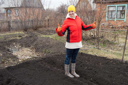 full length portrait of a smiling woman gardener showing thumb up