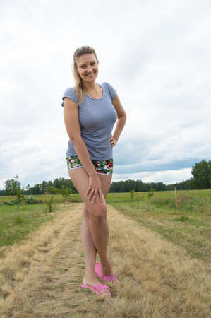 Smiling young woman in shorts and t-shirt posing on a background of grass and sky Stock Photo
