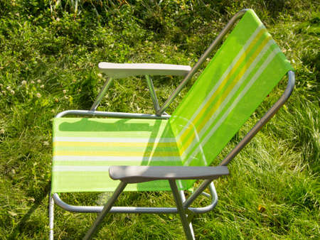Folding chair for camping on green grass.