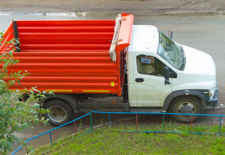 moving truck: New red dump truck with white cab is empty, ready for transportation. Stock Photo