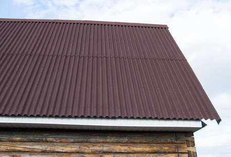 modern construction of the roof with red metal siding to a wooden house in the garden.