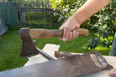 claw hammer: man holding the axe, working with construction tools in his garden Stock Photo