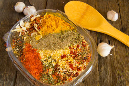 The range of oriental spices with spicy chilli, curry and a mixture of other spices on an old dark wooden table