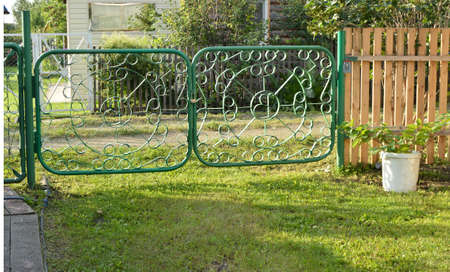 Green metal gate with a wicket - fence garden.
