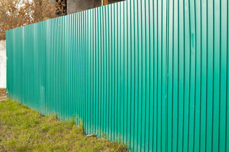 fence with green metal siding, the concept of security and protection.