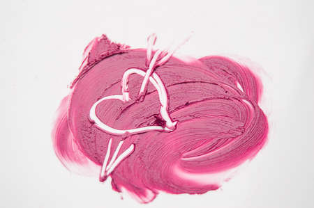 The texture of pink lipstick drawn heart pierced by an arrow, love, cheating, make-up.