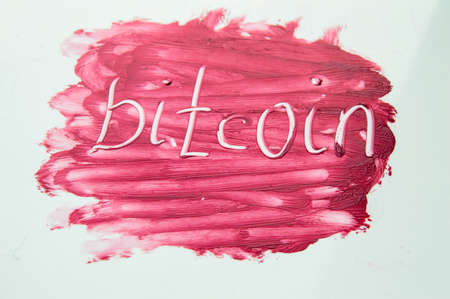 Cryptocurrency Bitcoin symbol on textured background red lipstick. Stock Photo