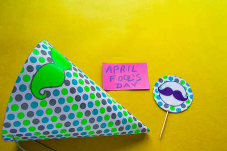 Cap, topper with a mustache and notes with the phrase April fools day on a yellow background Stock Photo