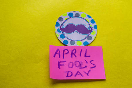 Paper topper with a painted mustache and the words April fools day, yellow background
