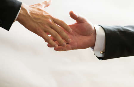 Businessmen in suits reach out to each other for handshake, help, deal, Finance Stock Photo