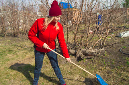 Young beautiful woman farmer cleans rake dry grass, wearing red jacket, boots and hat