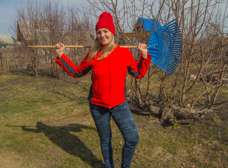 full length portrait of a smiling woman professional gardener with a rake, a beautiful blonde working in the garden Stock Photo