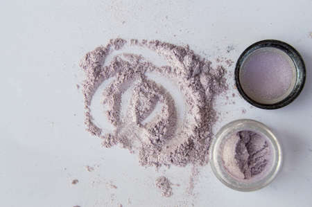 Pearlescent sparkling eye shadow scattered on the table, a jar of shadows