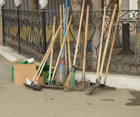 Equipment for cleaning the city street. Rake, shovel, broom stand near the fence of the Park