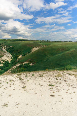 Beautiful view of grassy ravine on sky background with clouds, vertical shot