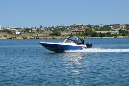 Motor boat moves along the sea along the shore, leaving a trail