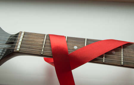 guitar, rock music and red ribbon - symbol of fight against AIDS