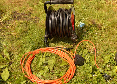 Coil with electric cable and extension cord on the grass, electric tools for construction works in the garden
