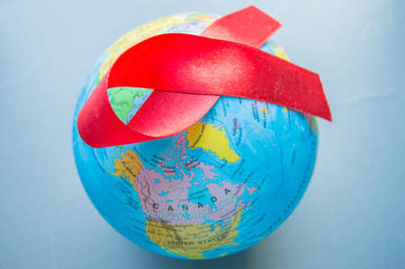 World AIDS day 1 December, close-up of world globe with red ribbon