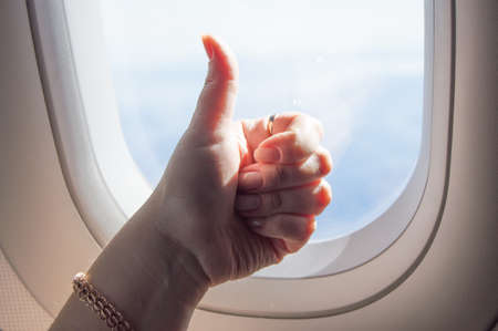 Gesture thumb up, OK sign, womans hand on the background of the WINDOW on the plane Standard-Bild