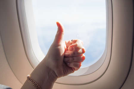 Gesture thumb up, OK sign, woman's hand on the background of the WINDOW on the plane.