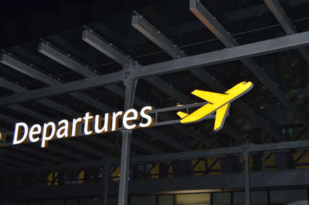 Information about the departure zone, signpost of the aircraft at the airport at night, the concept of travel.